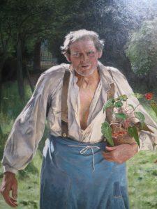 Homme âgé dans un jardin, un pot de fleur dans ses bras