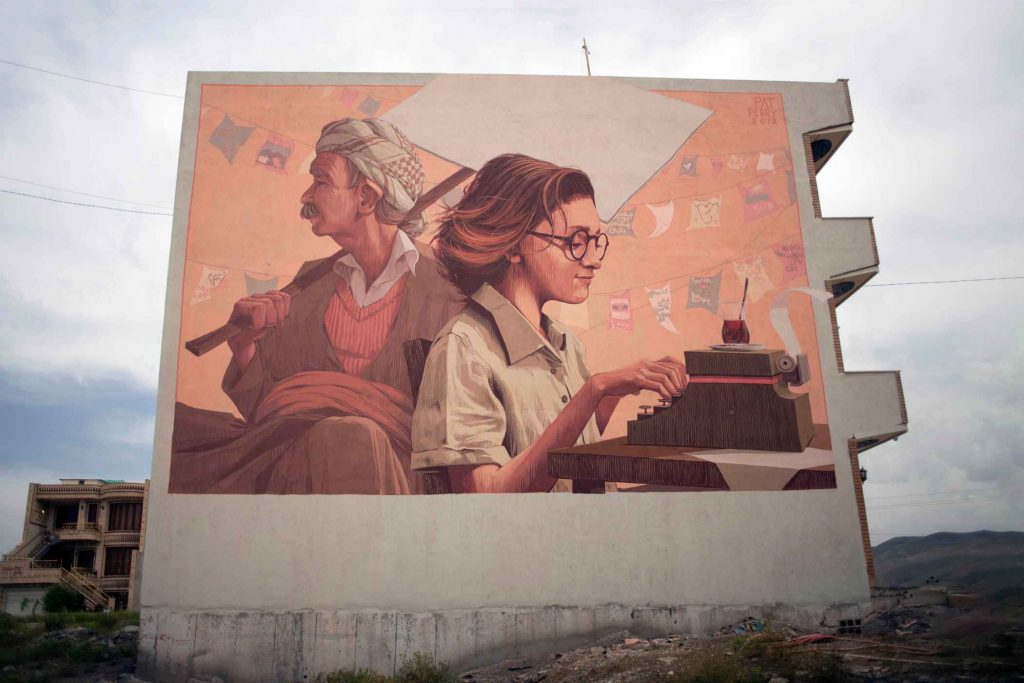 mur peint en Irak ,jeune femme tapant à la machine et en arrière plan un homme enrubanné avec un panneau sur l'épaule